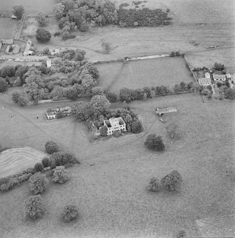 Oblique aerial view centred on the remains of the country house with stables, walled garden, tower house, farmhouse and cottages adjacent, taken from the SSE.