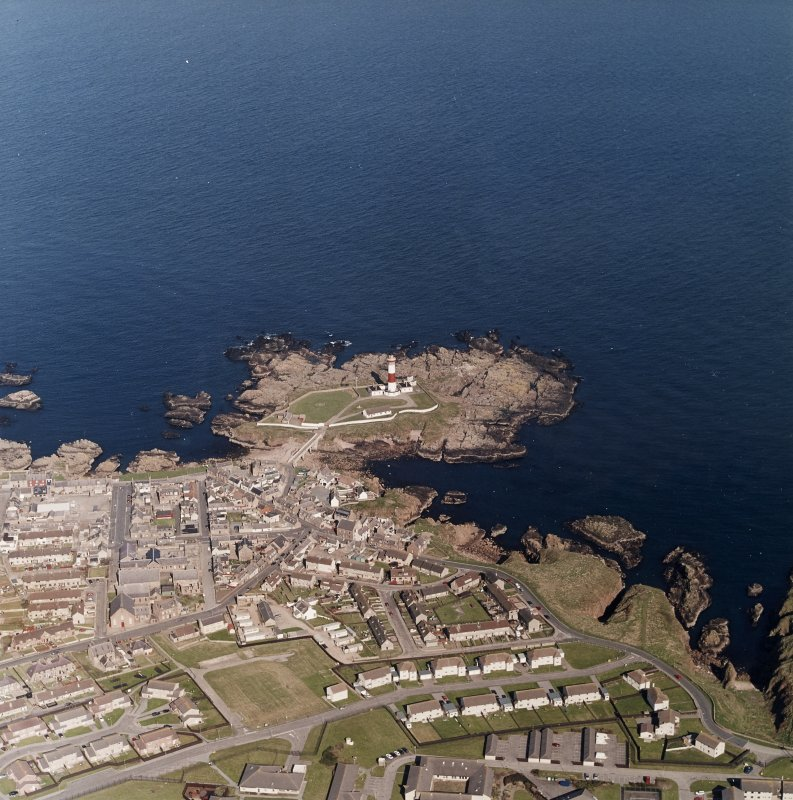 Oblique aerial view centred on the lighthouse with the school and churches adjacent, taken from the W.