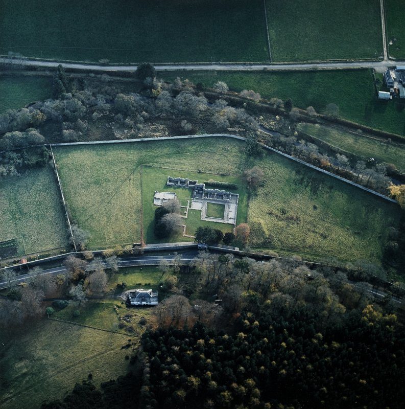 Oblique aerial view centred on the remains of the abbey with the walled garden and house adjacent, taken from the N.