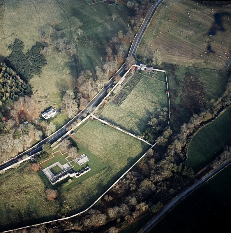 Oblique aerial view centred on the remains of the abbey with the walled garden and house adjacent, taken from the SW.