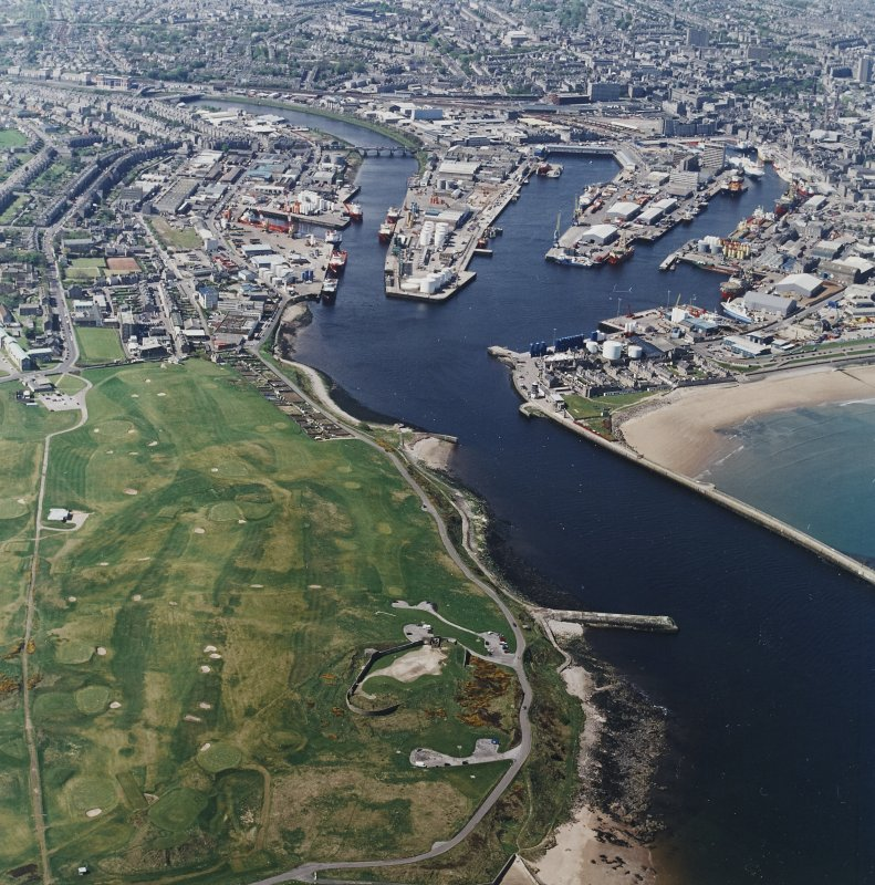 Oblique aerial view centred on the remains of the coastal battery with breakwater adjacent and harbour in background, taken from the E.