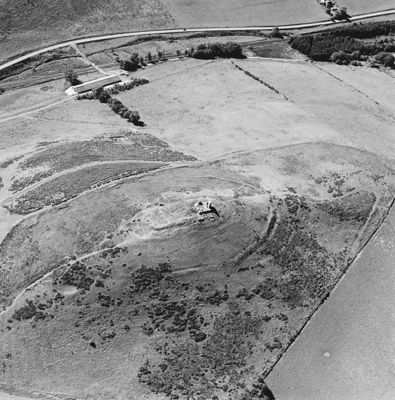 Oblique aerial view of Dunnideer centred on the remains of a fort and tower-house, taken from the NE.