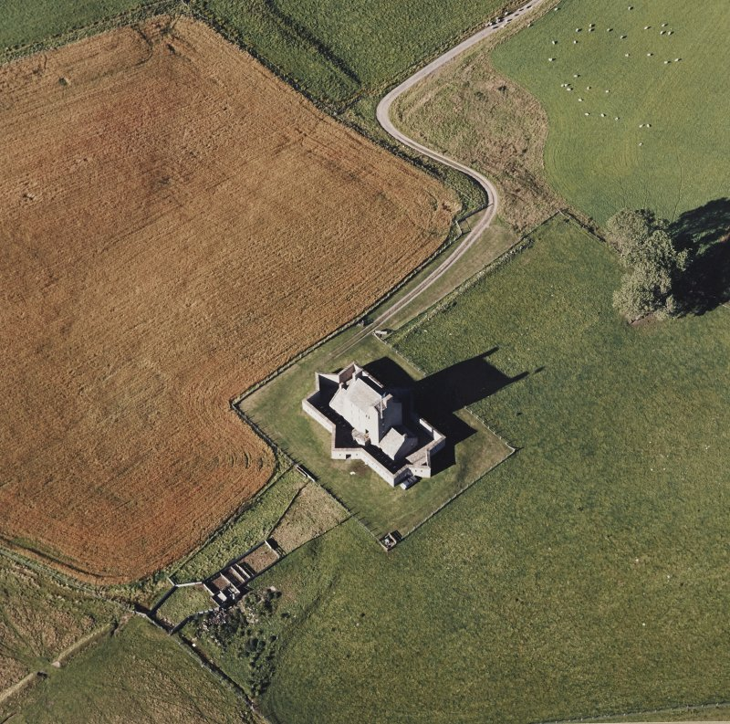 Oblique aerial view of Corgarff castle centred on the tower-house with the remains of a pond, farmstead and the cropmarks of a building adjacent, taken from the SSE.