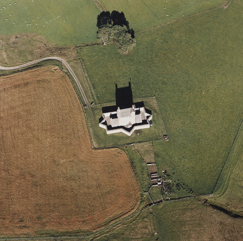 Oblique aerial view of Corgarff castle centred on the tower-house with the remains of a pond, farmstead and the cropmarks of a building adjacent, taken from the SSW.