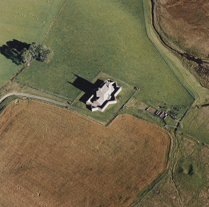 Oblique aerial view of Corgarff castle centred on the tower-house with the remains of a pond, farmstead and the cropmarks of a building adjacent, taken from the W.