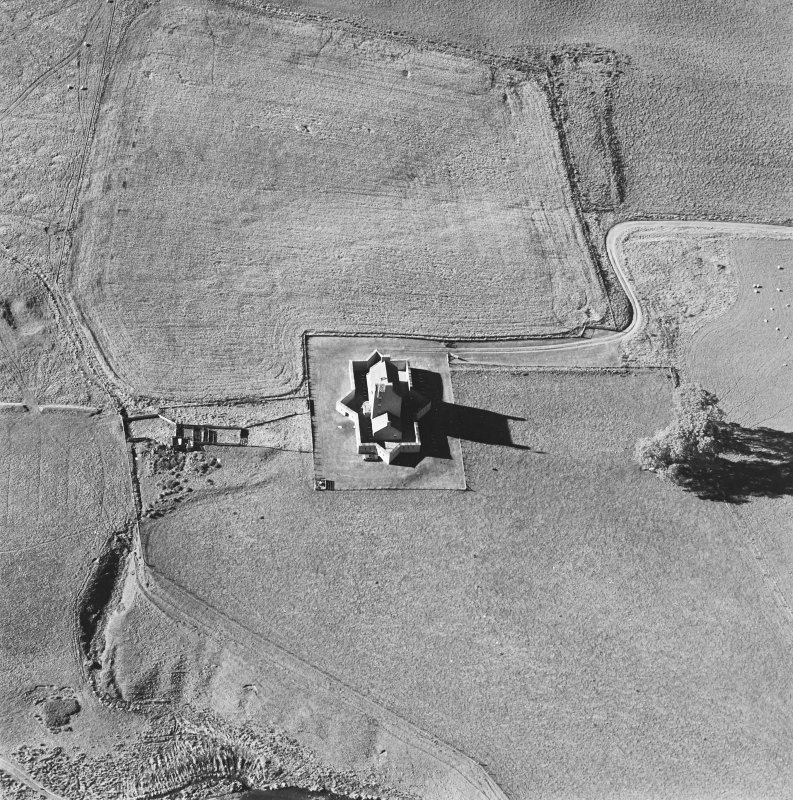 Oblique aerial view of Corgarff castle centred on the tower-house with the remains of a pond, quarry, farmstead, building and the cropmarks of a building adjacent, taken from the ESE.