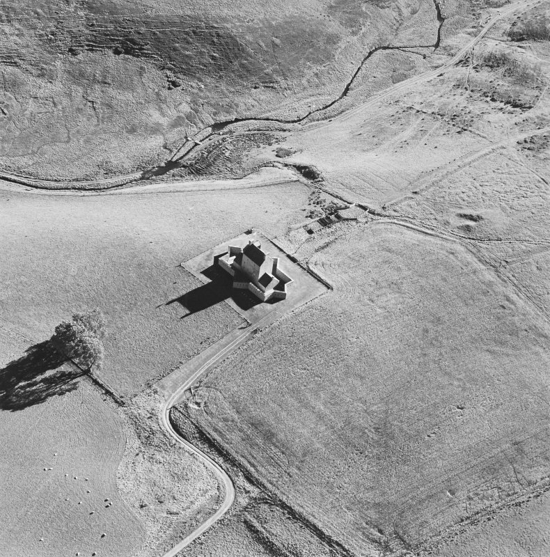 Oblique aerial view of Corgarff castle centred on the tower-house with the remains of a pond, quarry, farmstead and the cropmarks of a building adjacent, taken from the NNW.