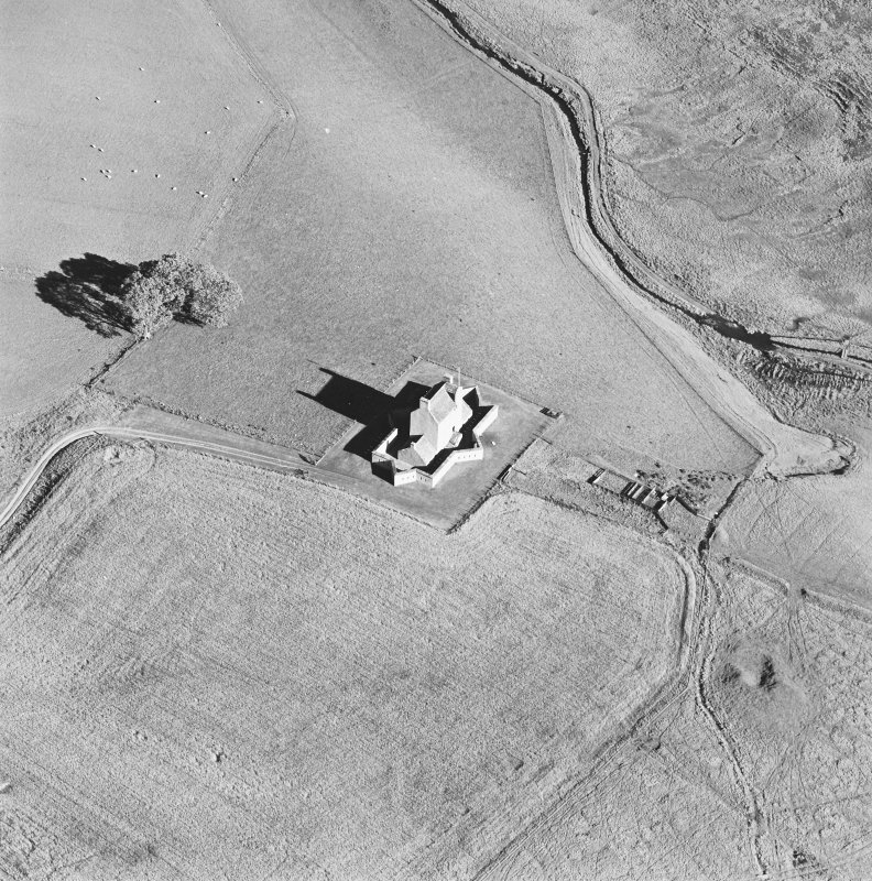 Oblique aerial view of Corgarff castle centred on the tower-house with the remains of a pond, quarry and the cropmarks of a building adjacent, taken from the WSW.