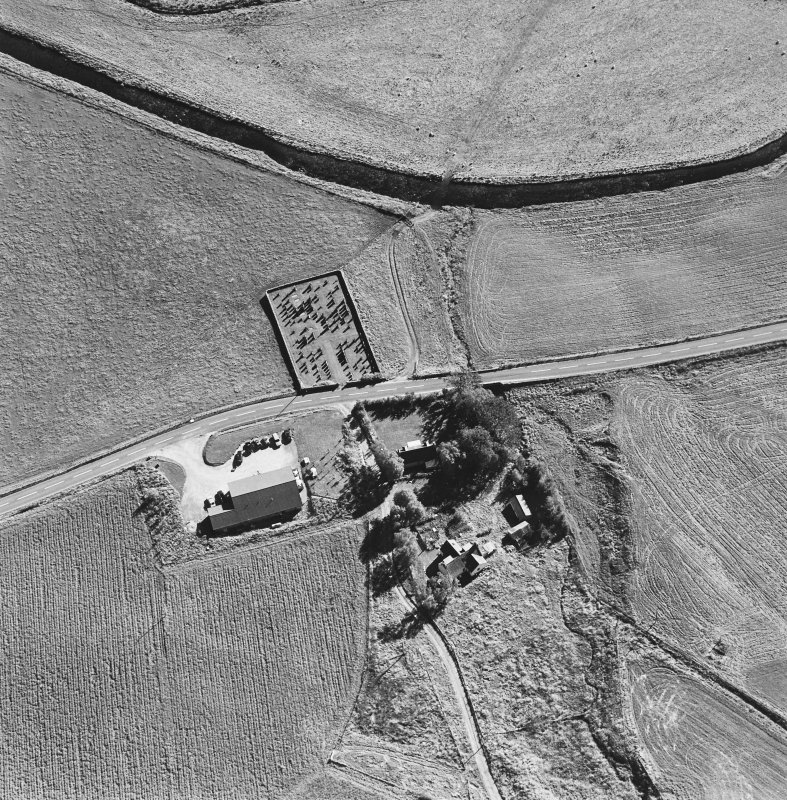 Oblique aerial view of Corriehoul centred on a burial-ground with a farmstead across the road, taken from the N.