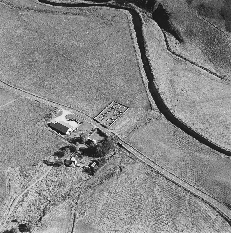 Oblique aerial view of Corriehoul centred on a burial-ground with a farmstead across the road, taken from the NW.