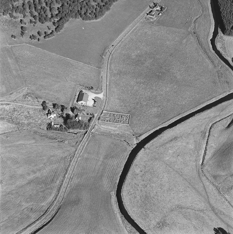 Oblique aerial view of Corriehoul centred on a burial-ground with a farmstead across the road, taken from the WSW.