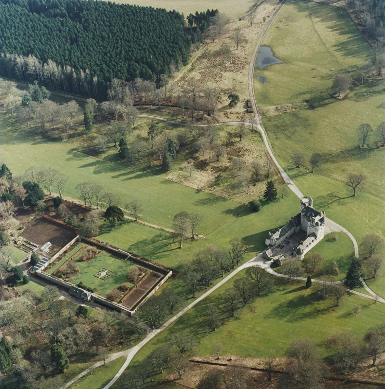 Oblique aerial view of the tower-house with walled garden adjacent, taken from the NW.