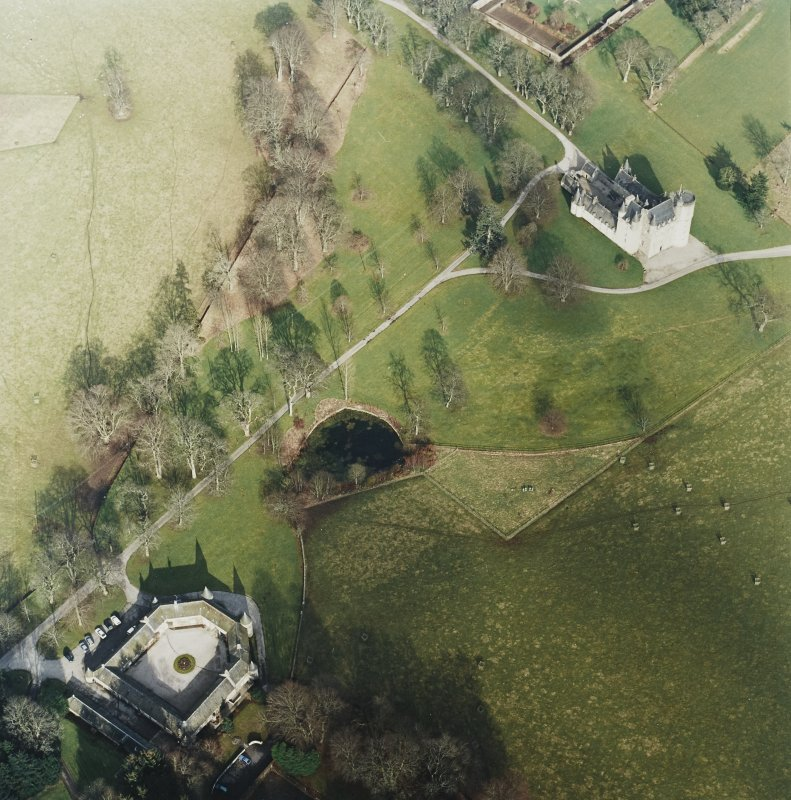 Oblique aerial view centred on the tower-house with the stable block adjacent, taken from the SW.