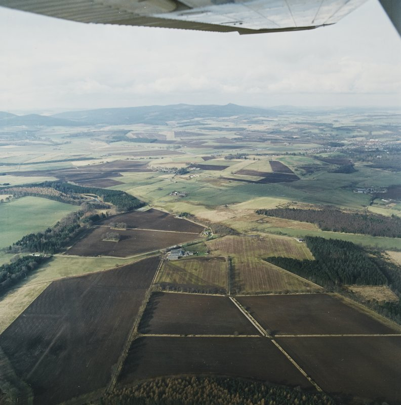 General oblique aerial view looking over the Greenmoss farmsteading towards Bennachie, taken from the SE.
