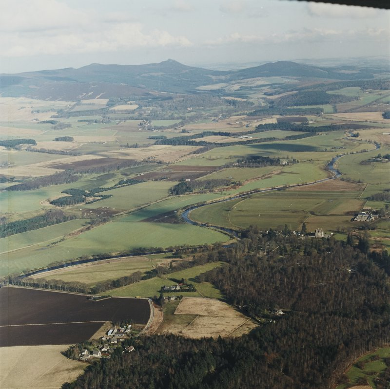 General oblique aerial view looking across the Howe of Alford down the River Don towards Bennachie, taken from the SW.