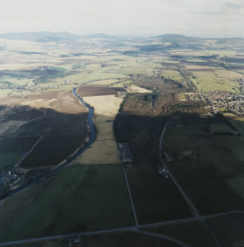 General oblique aerial view looking across the Howe of Alford down the River Don towards Bennachie and Cairn William with Montgarrie and Alford in the middle-distance, taken from the W.  The bottom half of the image is in shadow.