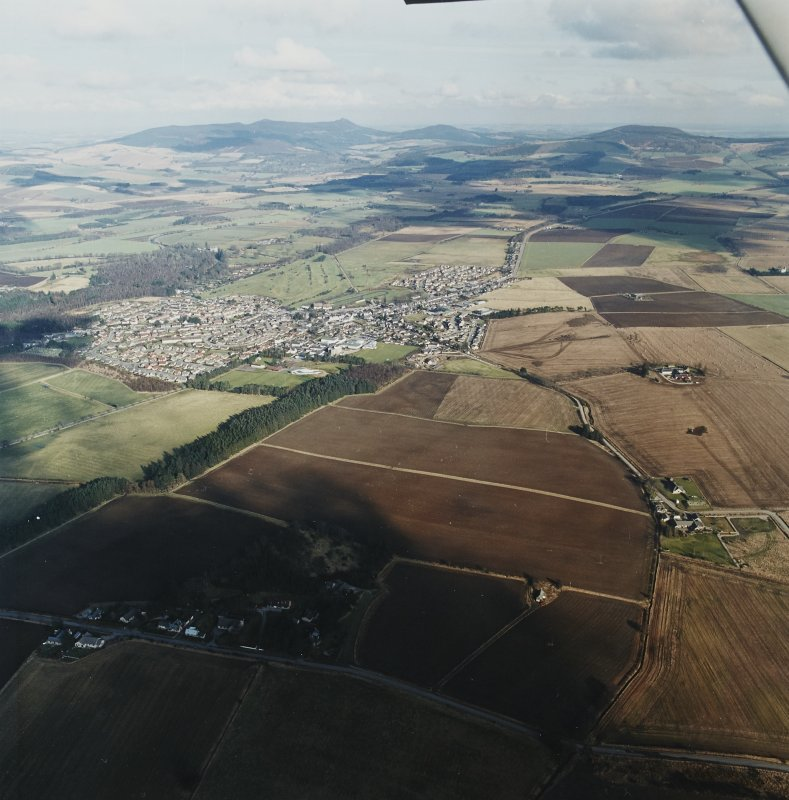 General oblique aerial view looking across the Howe of Alford towards Bennachie and Cairn William with Alford in the middle-distance, taken from the SW.