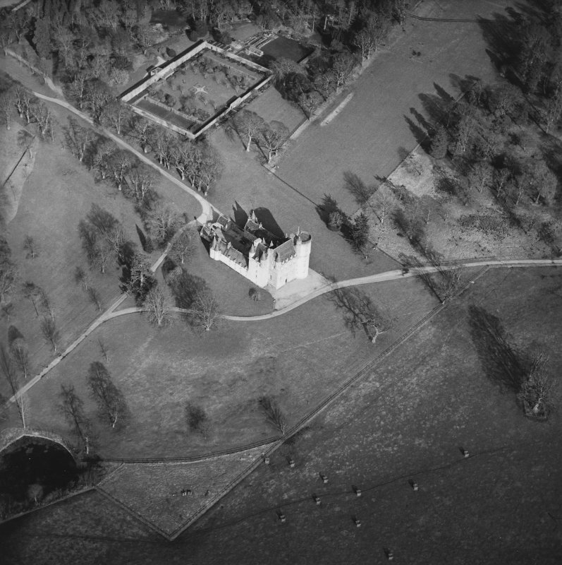 Oblique aerial view of the tower-house with walled garden adjacent, taken from the SW.
