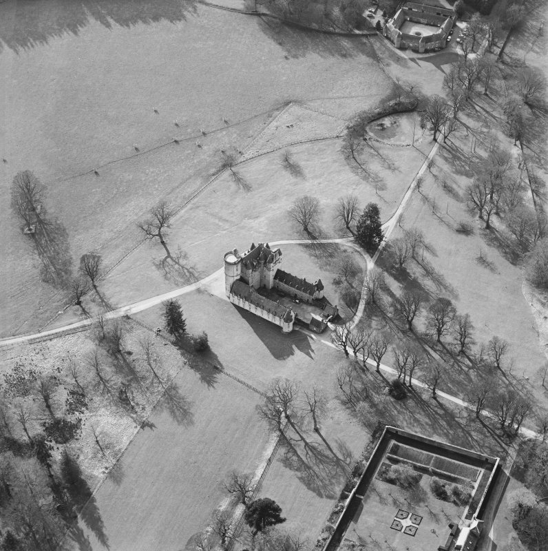 Oblique aerial view of the tower-house with the stable block adjacent, taken from the NE.