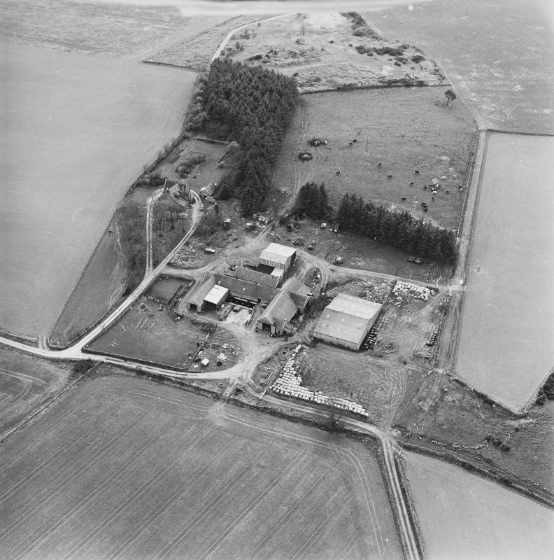 General oblique aerial view centred on the farmstead with the disused quarry adjacent, taken from the NE.