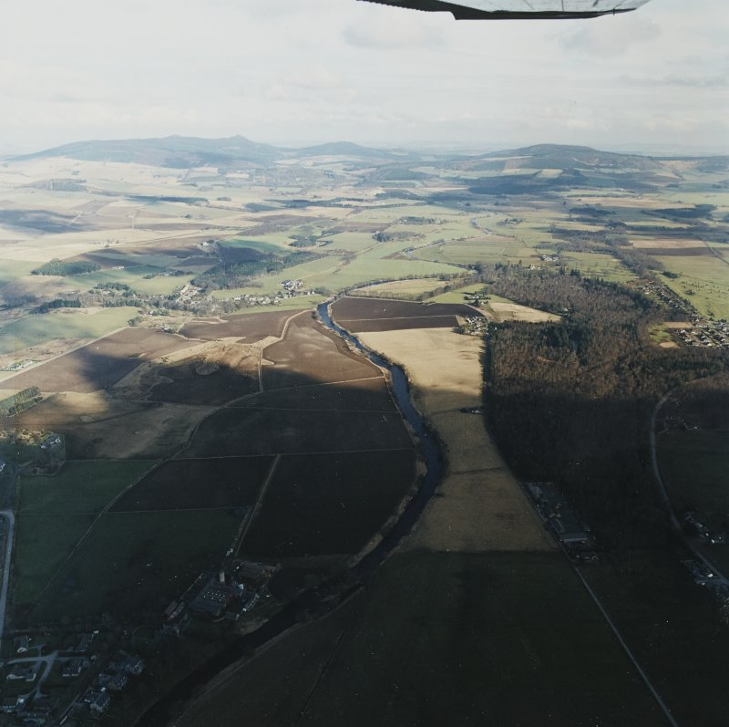General oblique aerial view looking across the Howe of Alford down the River Don towards Bennachie and Cairn William with Montgarrie in the middle-distance, taken from the W.  The bottom half of the image is in shadow.