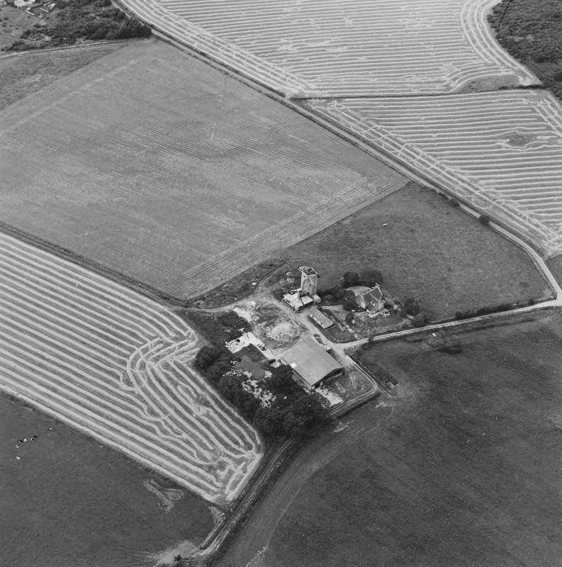 Oblique aerial view of Blervie Castle centred on the remains of a castle or tower-house with attached and adjacent farm buildings, taken from the E.