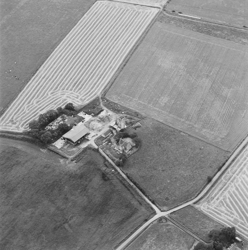 Oblique aerial view of Blervie Castle centred on the remains of a castle or tower-house with attached and adjacent farm buildings, taken from the NNE.