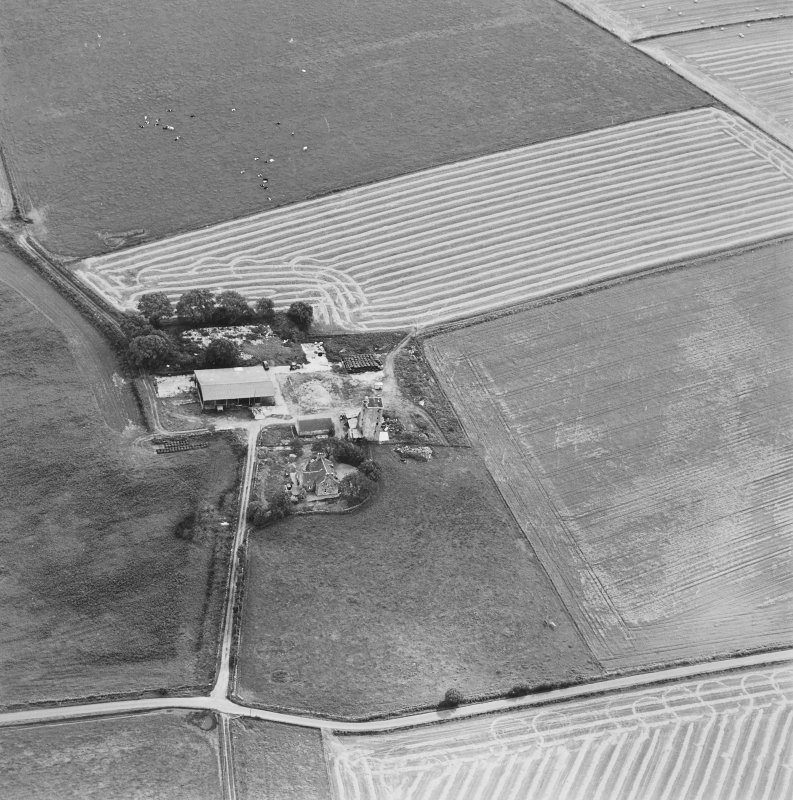 Oblique aerial view of Blervie Castle centred on the remains of a castle or tower-house with attached and adjacent farm buildings, taken from the NNW.