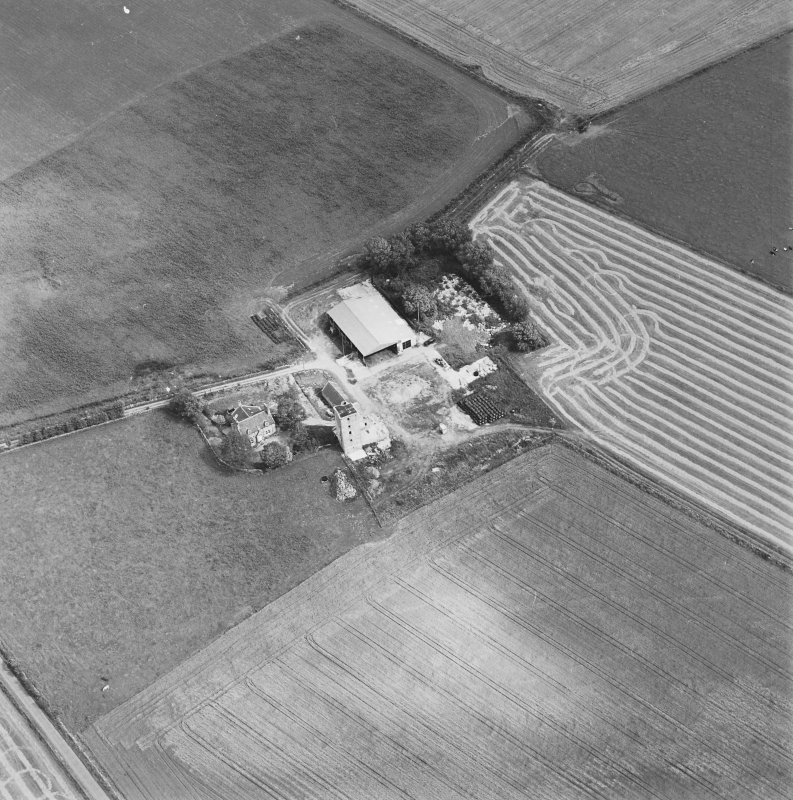 Oblique aerial view of Blervie Castle centred on the remains of a castle or tower-house with attached and adjacent farm buildings, taken from the WSW.
