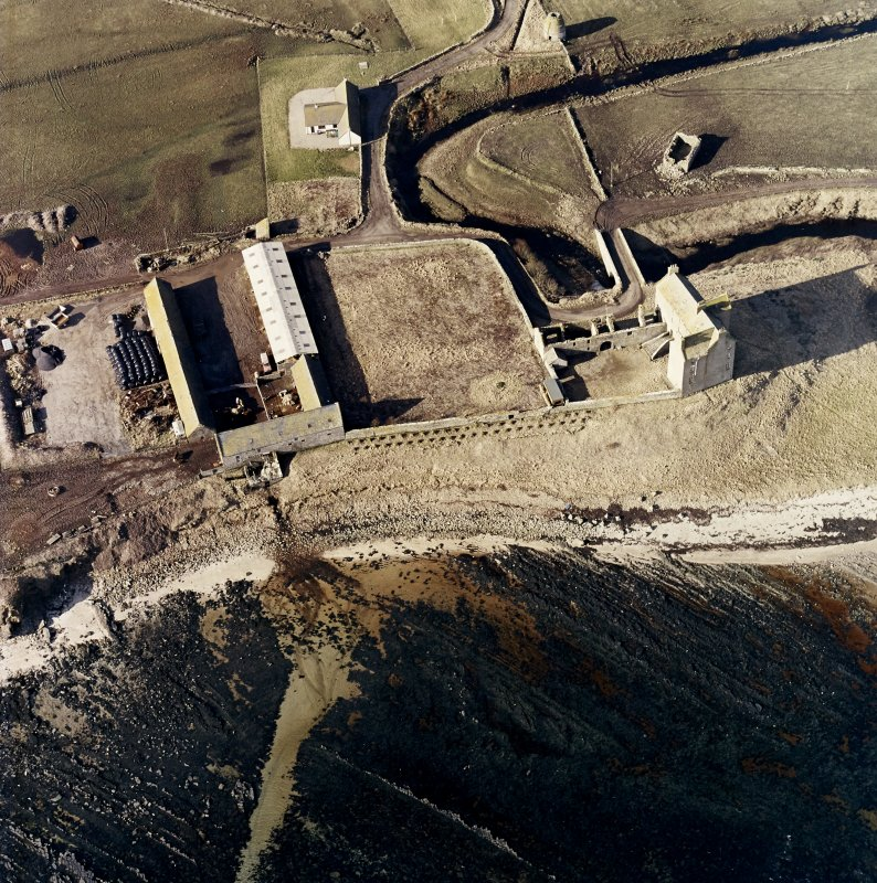 Oblique aerial view of the castle, bridge, farmsteading and the remains of the mausoleum, dovecot and anti-tank blocks, taken from the NE.