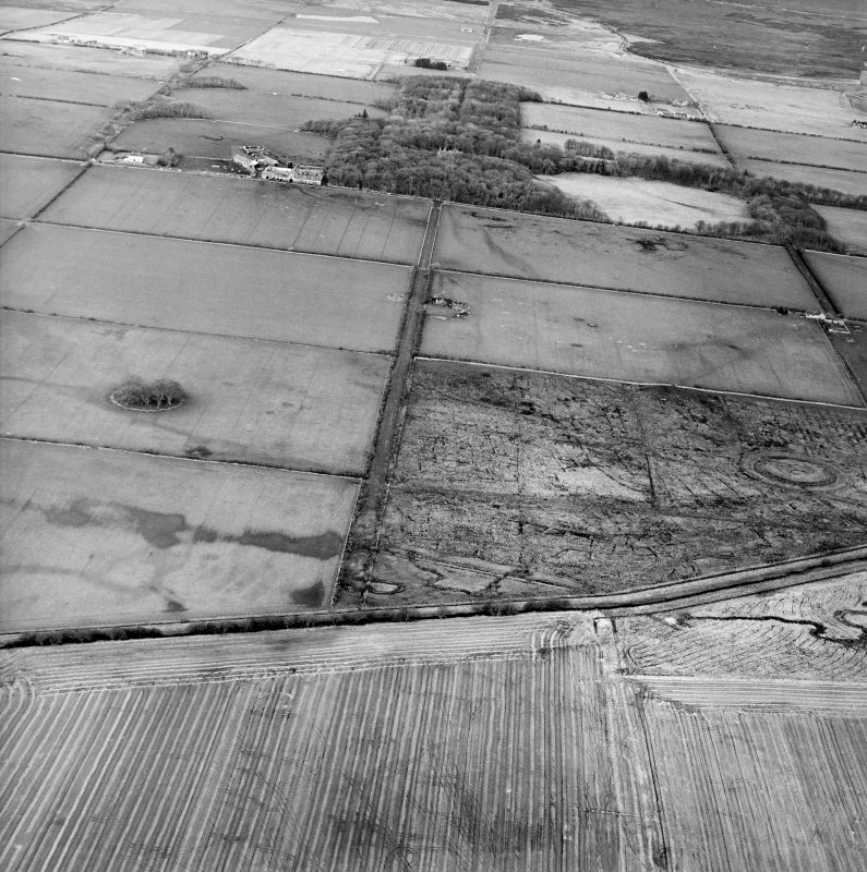 General oblique aerial view looking across the remains of the fort and possible broch towards the country house and farmsteading, taken from the SSW