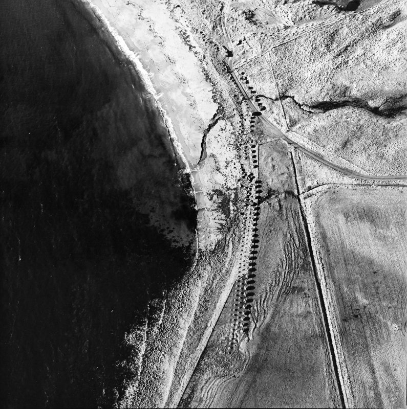 Oblique aerial view of Freswick Bay centred on the remains of anti-tank blocks and a road block, taken from the NE.