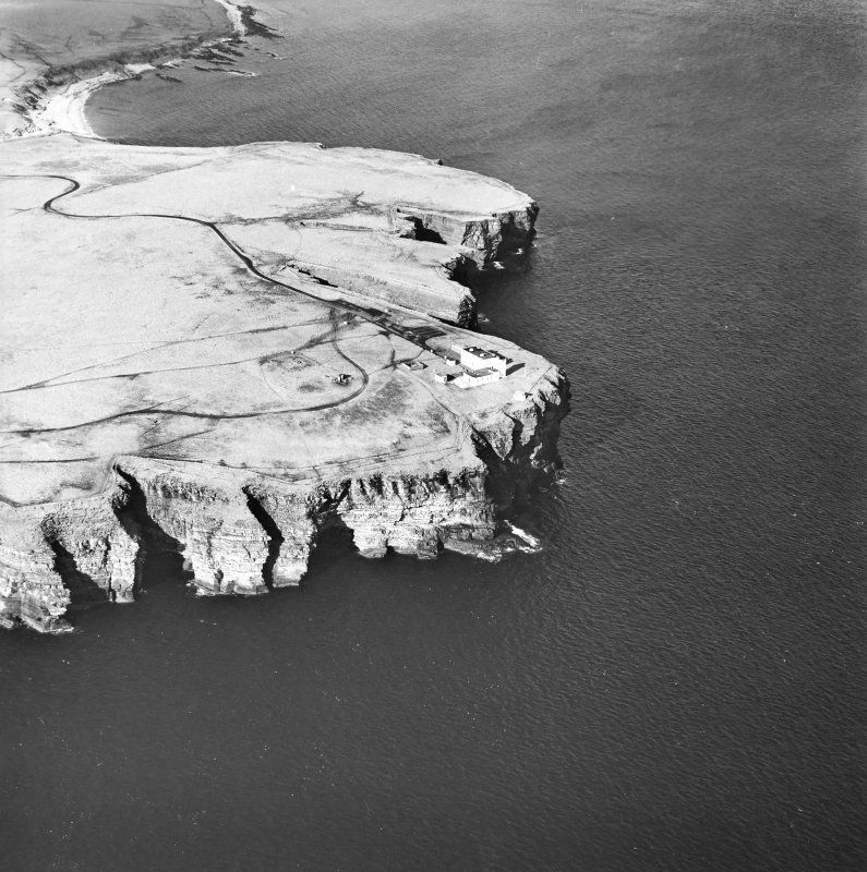 General oblique aerial view looking over the cliffs at Duncansby Head to the lighthouse and the remains of the possible broch, taken from the SE.