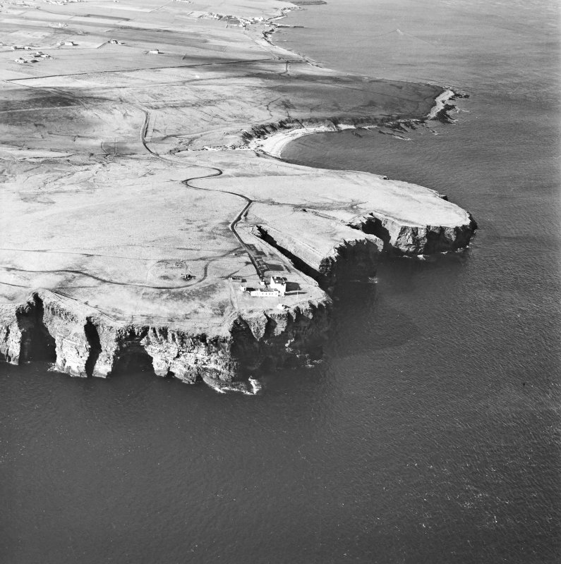 General oblique aerial view looking over the cliffs at Duncansby Head to the lighthouse and the remains of the possible broch, taken from the E.