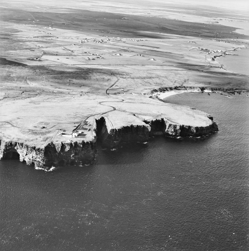 General oblique aerial view looking over the cliffs at Duncansby Head to the lighthouse and the remains of the possible broch, taken from the ENE.