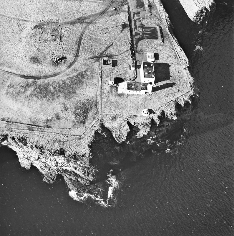 Oblique aerial view centred on the lighthouse and the remains of the possible broch, taken from the NE.