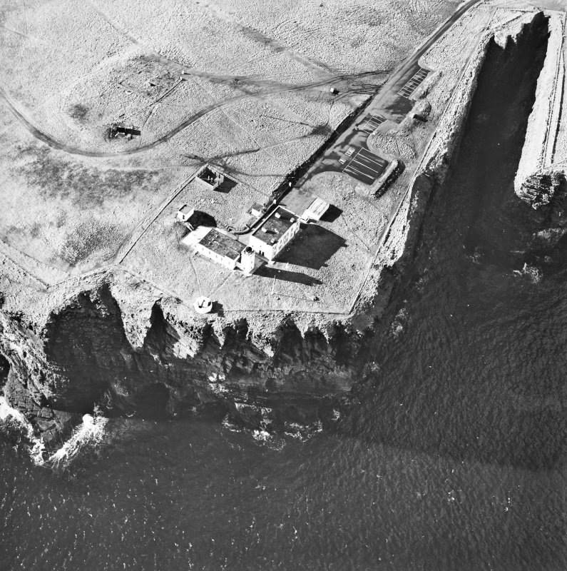 Oblique aerial view centred on the lighthouse and the remains of the possible broch, taken from the NNE.