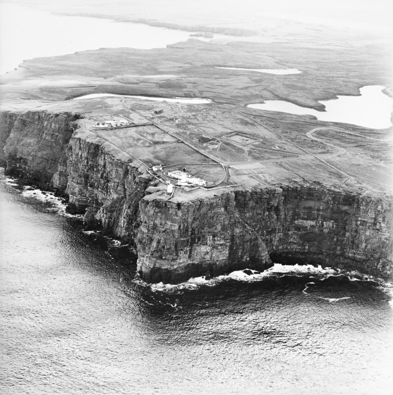 General oblique aerial view looking over the cliffs at Easter Head, Dunnet, to the lighthouse, radar station and the remains of the cairn, taken from the NW.