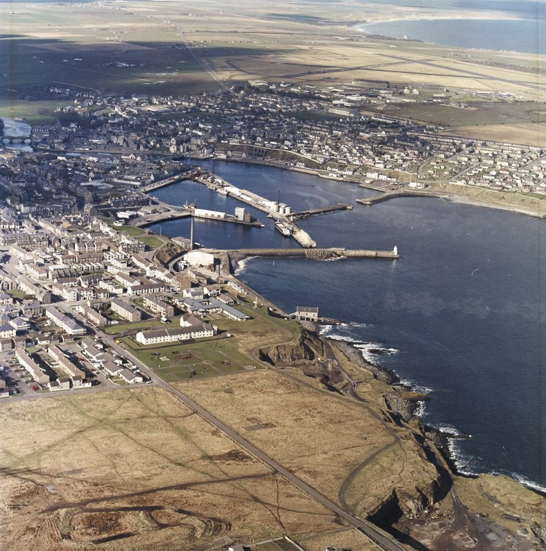 General oblique aerial view centred on the harbour and the town, taken from the SE.