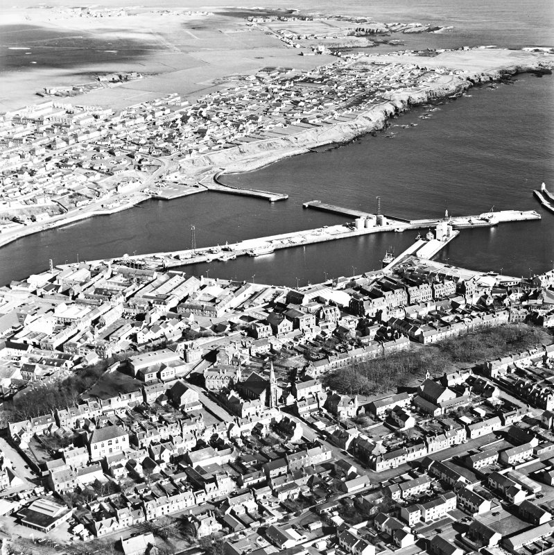 Oblique aerial view centred on the harbour with the town adjacent, taken from the SW.