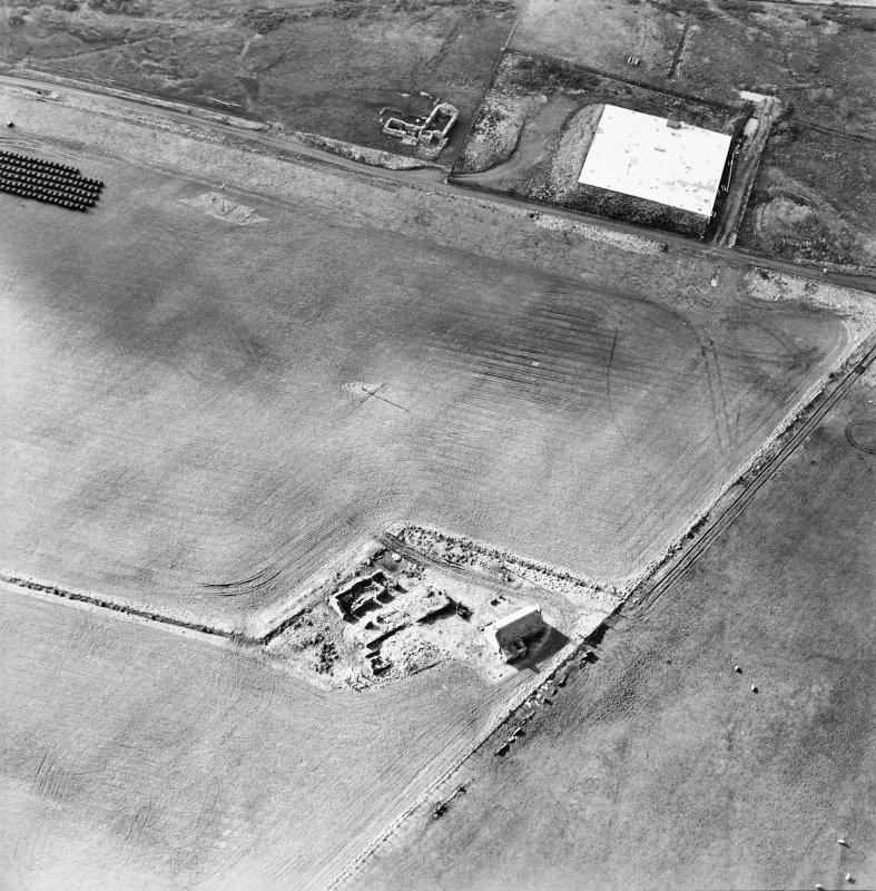 Oblique aerial view of the reservoir and the remains of the buildings, farmstead and chambered cairn, taken from the NE.