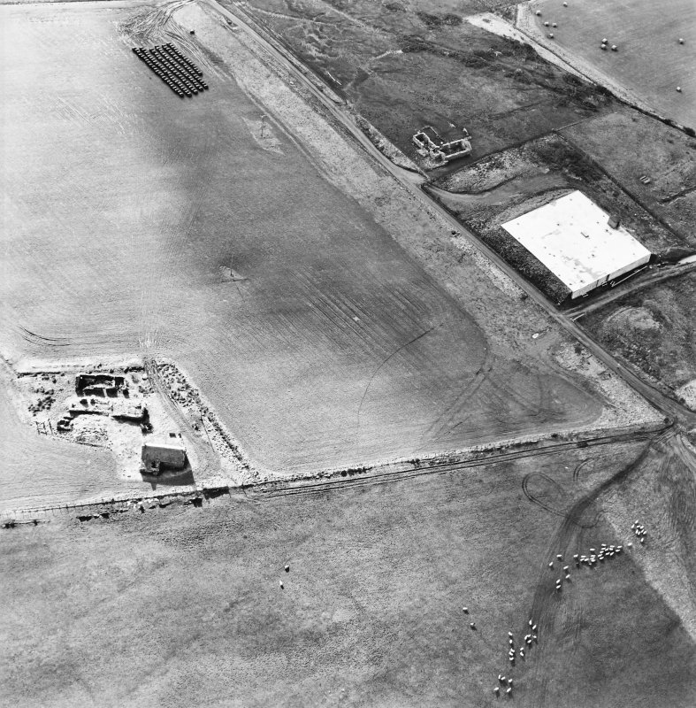 Oblique aerial view of the reservoir and the remains of the buildings, farmstead and chambered cairn, taken from the N.