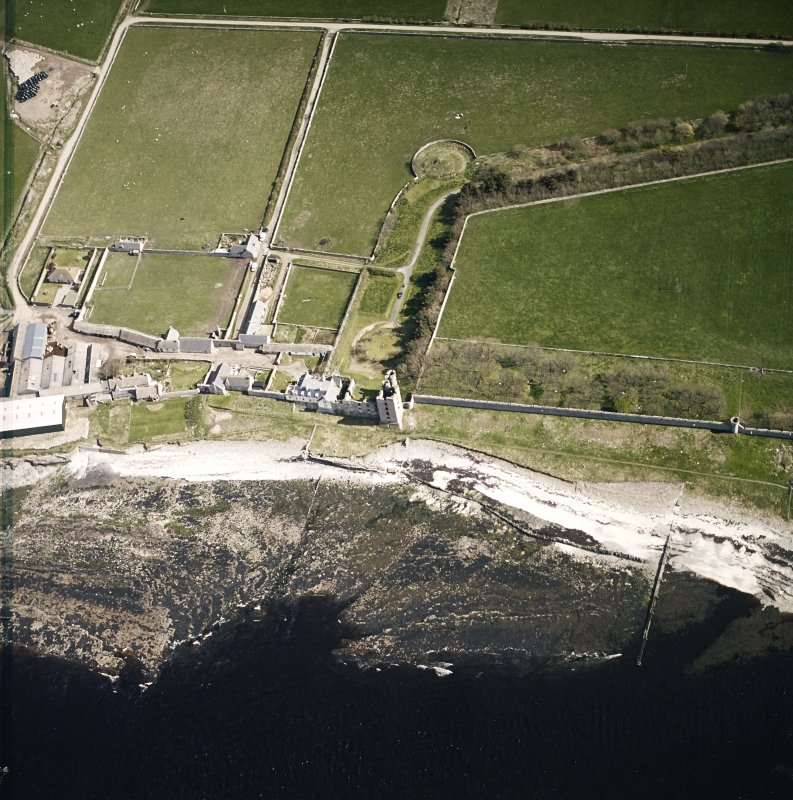 Oblique aerial view centred on the remains of the castle with the farmsteading adjacent, taken from the NW.