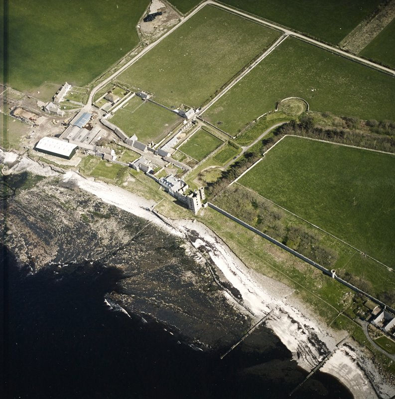 Oblique aerial view centred on the remains of the castle with the farmsteading adjacent, taken from the WNW.