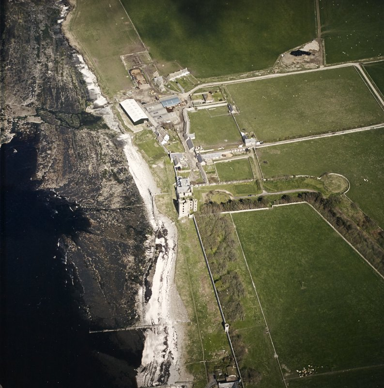Oblique aerial view centred on the remains of the castle with the farmsteading adjacent, taken from the WSW.