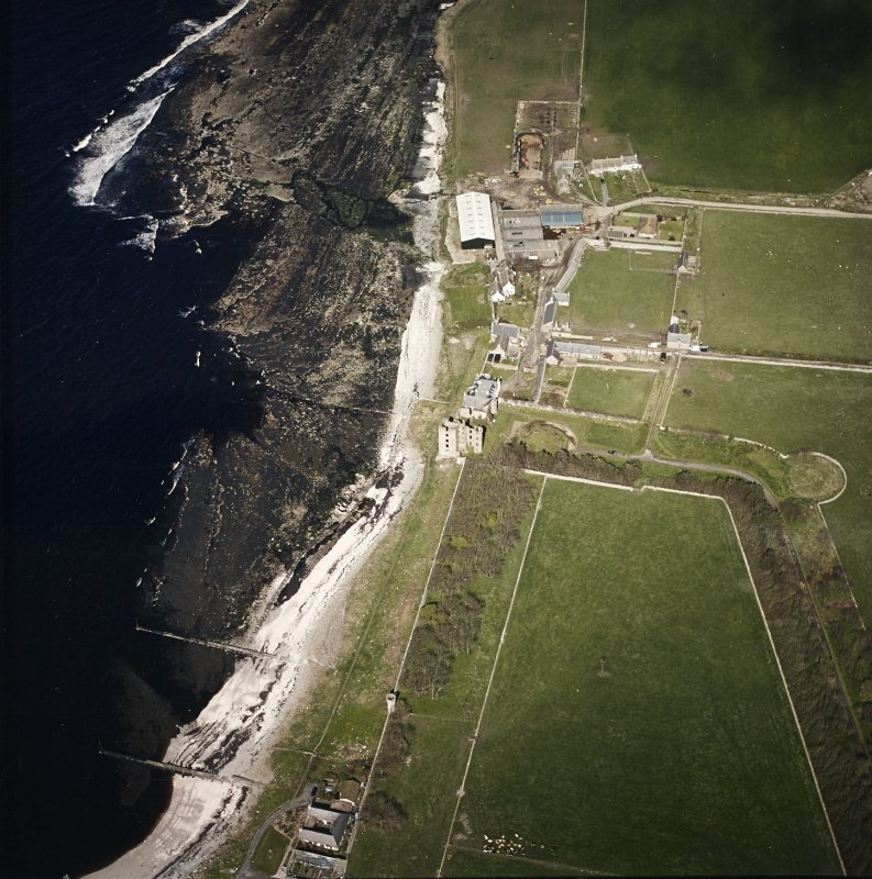Oblique aerial view centred on the remains of the castle with the farmsteading adjacent, taken from the SW.