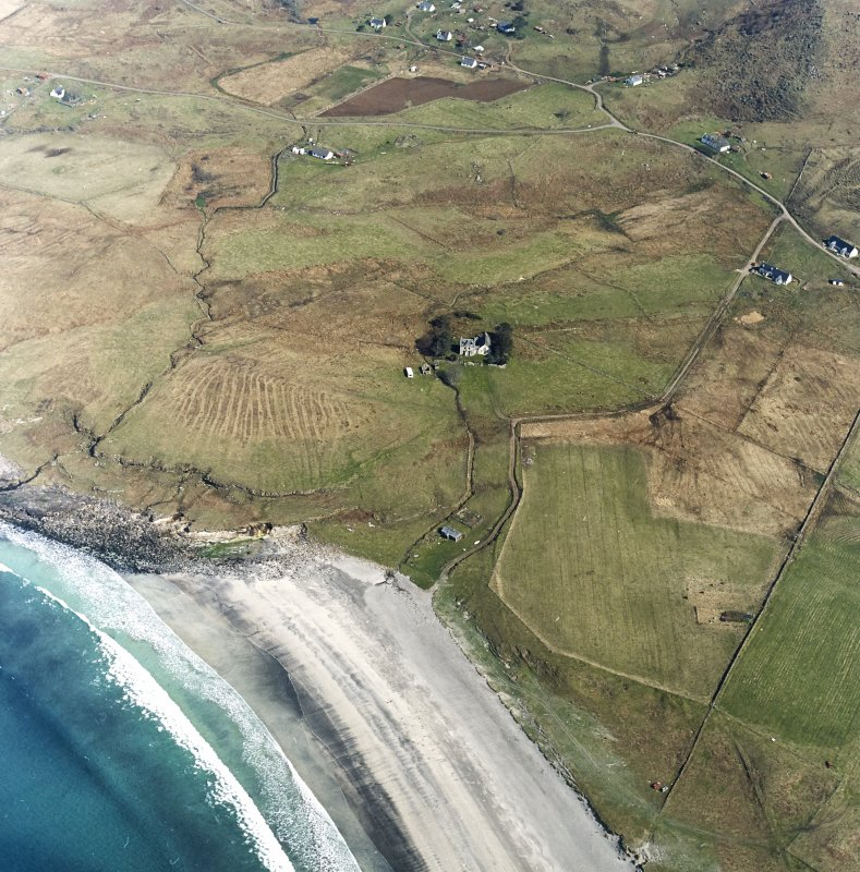 Oblique aerial view centred on the church, crofting township and field-system, taken from the SW.