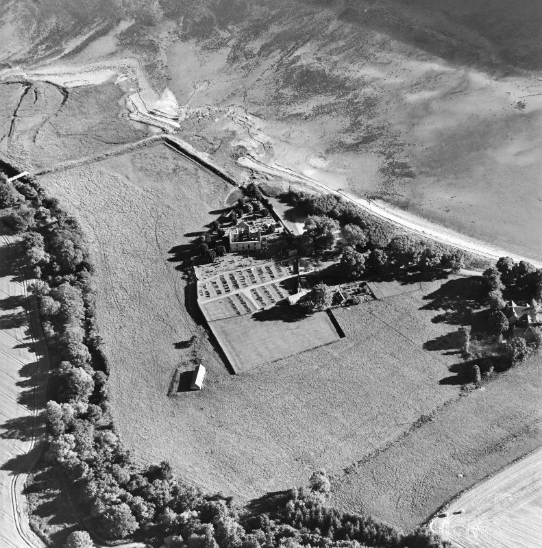 Oblique aerial view centred on the church, burial ground, farmsteading and barn with saltings adjacent, taken from the N.