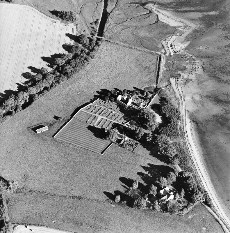 Oblique aerial view centred on the church, burial ground, farmsteading and barn with saltings adjacent, taken from the WNW.