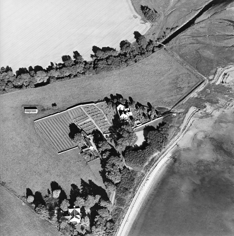 Oblique aerial view centred on the church, burial ground, farmsteading and barn with saltings adjacent, taken from the W.